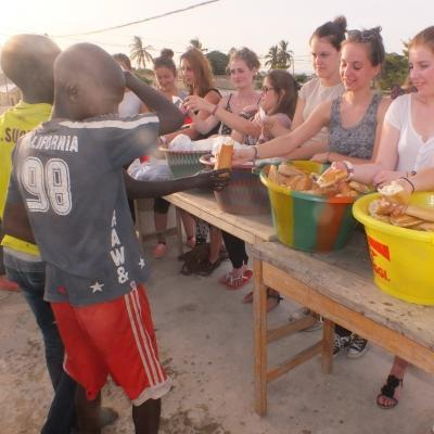 A group hands out food while they volunteer with children in Senegal.